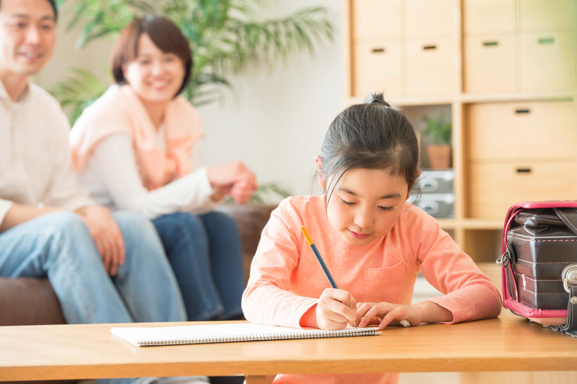 リビングで勉強する女の子と見守る両親