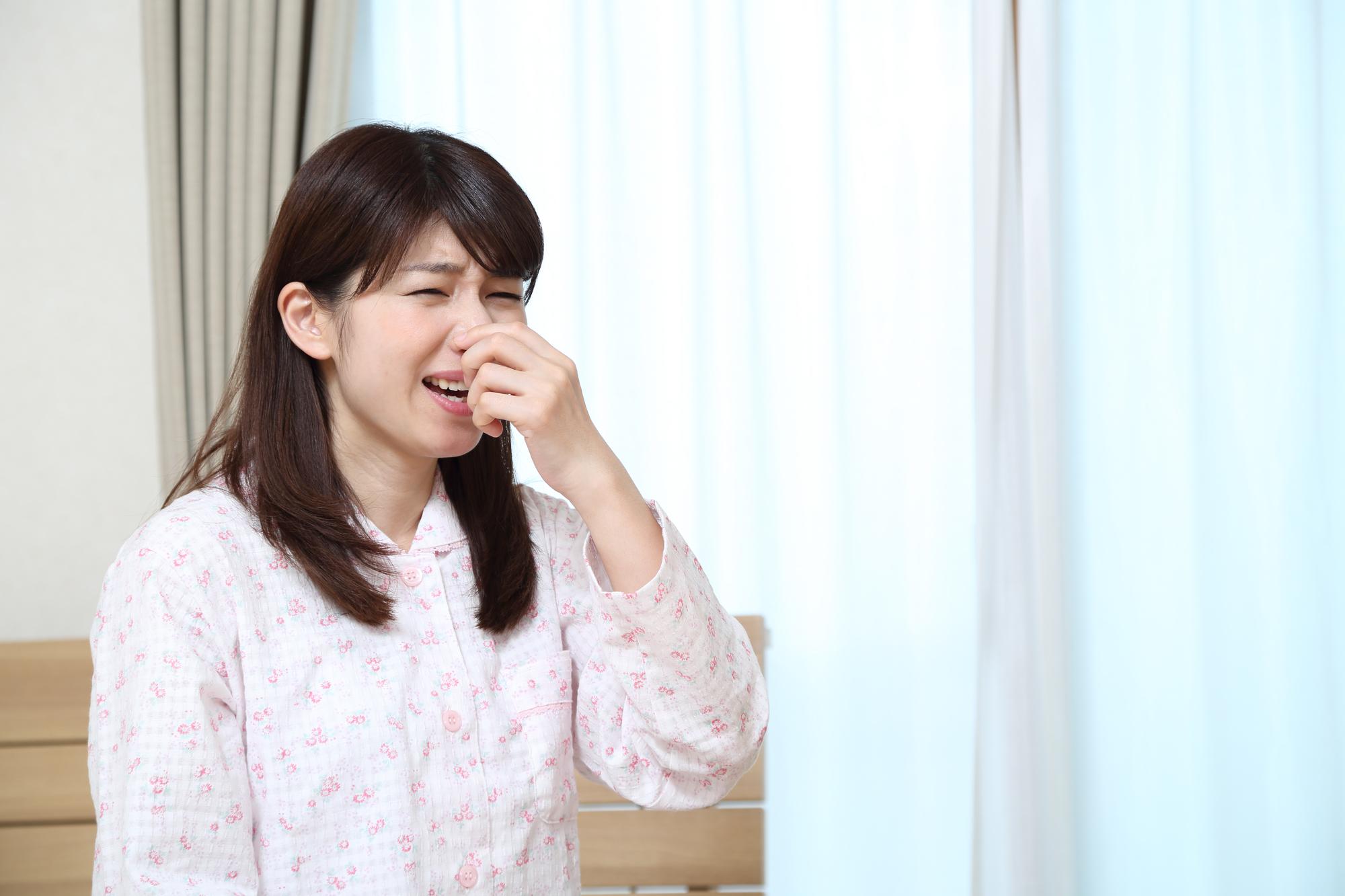 くしゃみをするパジャマの女性