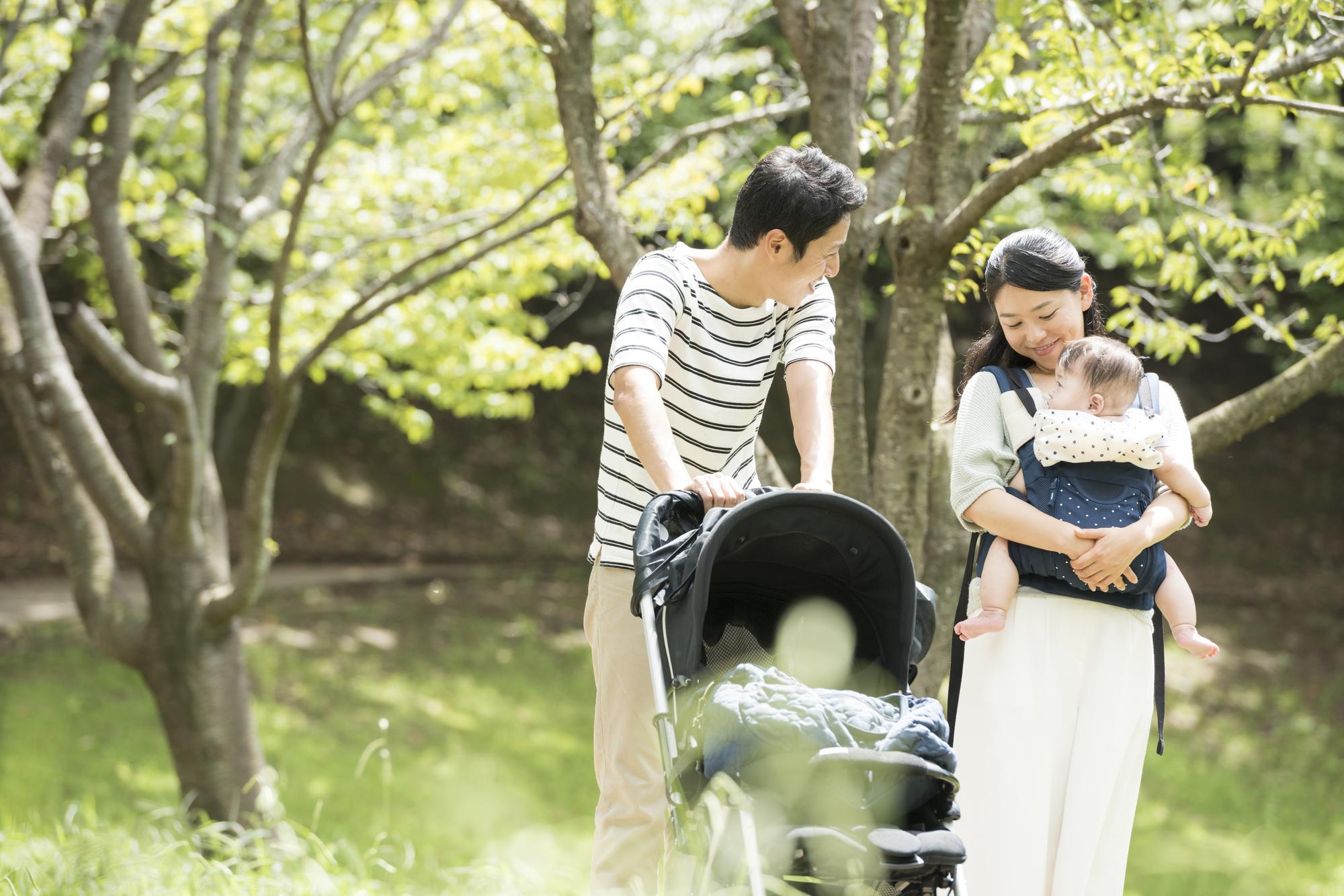 公園で散歩する赤ちゃんと両親