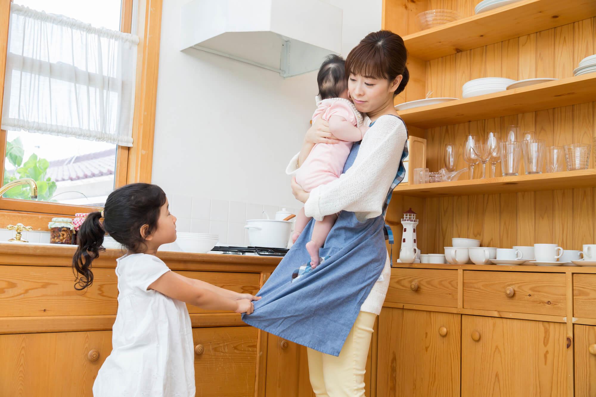 赤ちゃんを抱っこするお母さんとかまってほしい女の子