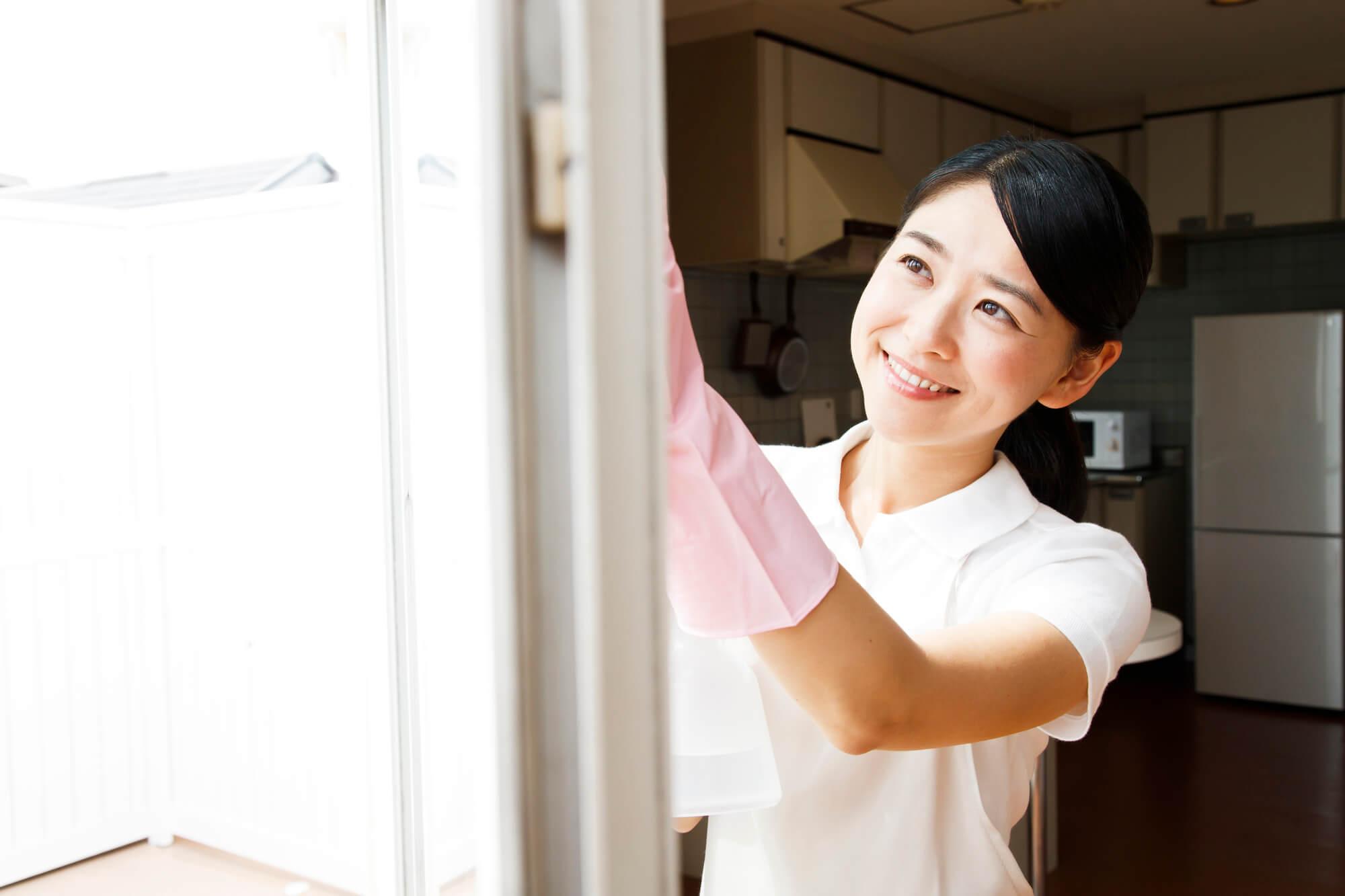 窓ガラスを掃除する女性