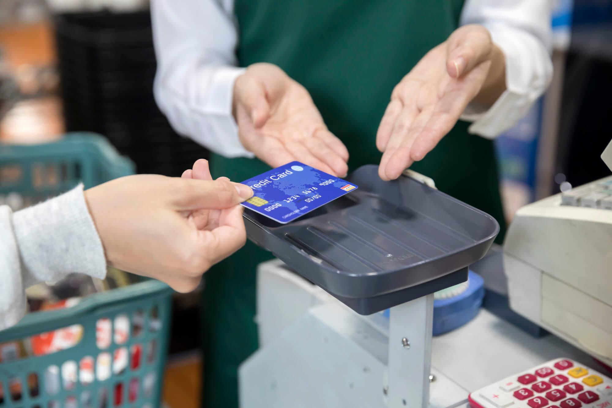 スーパーでクレジット払いをする女性手元