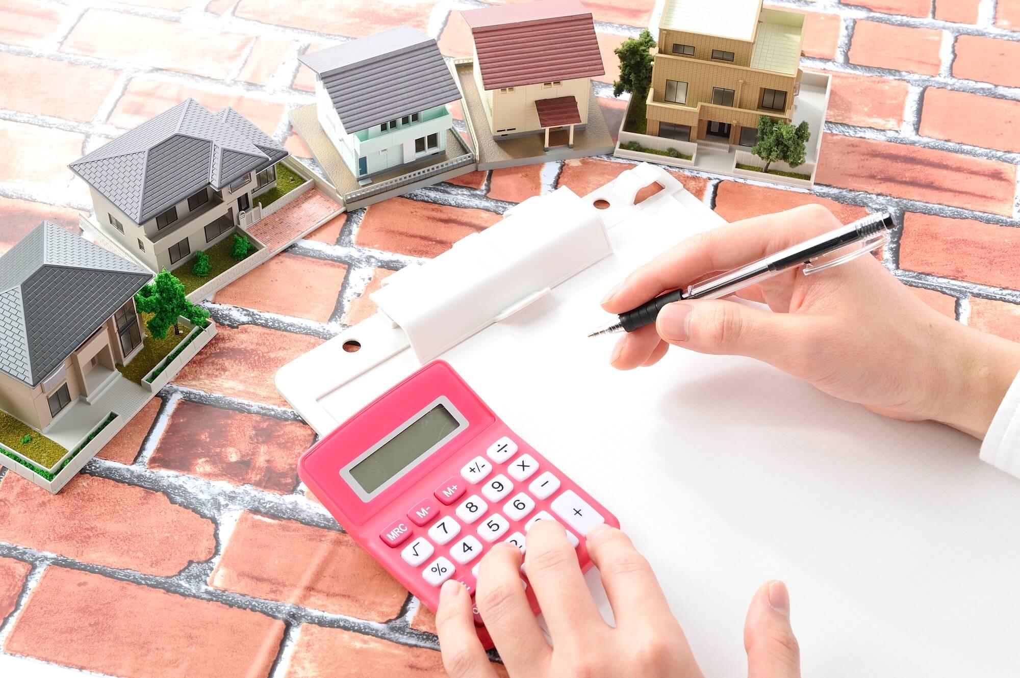 住宅模型とセールスマンの手