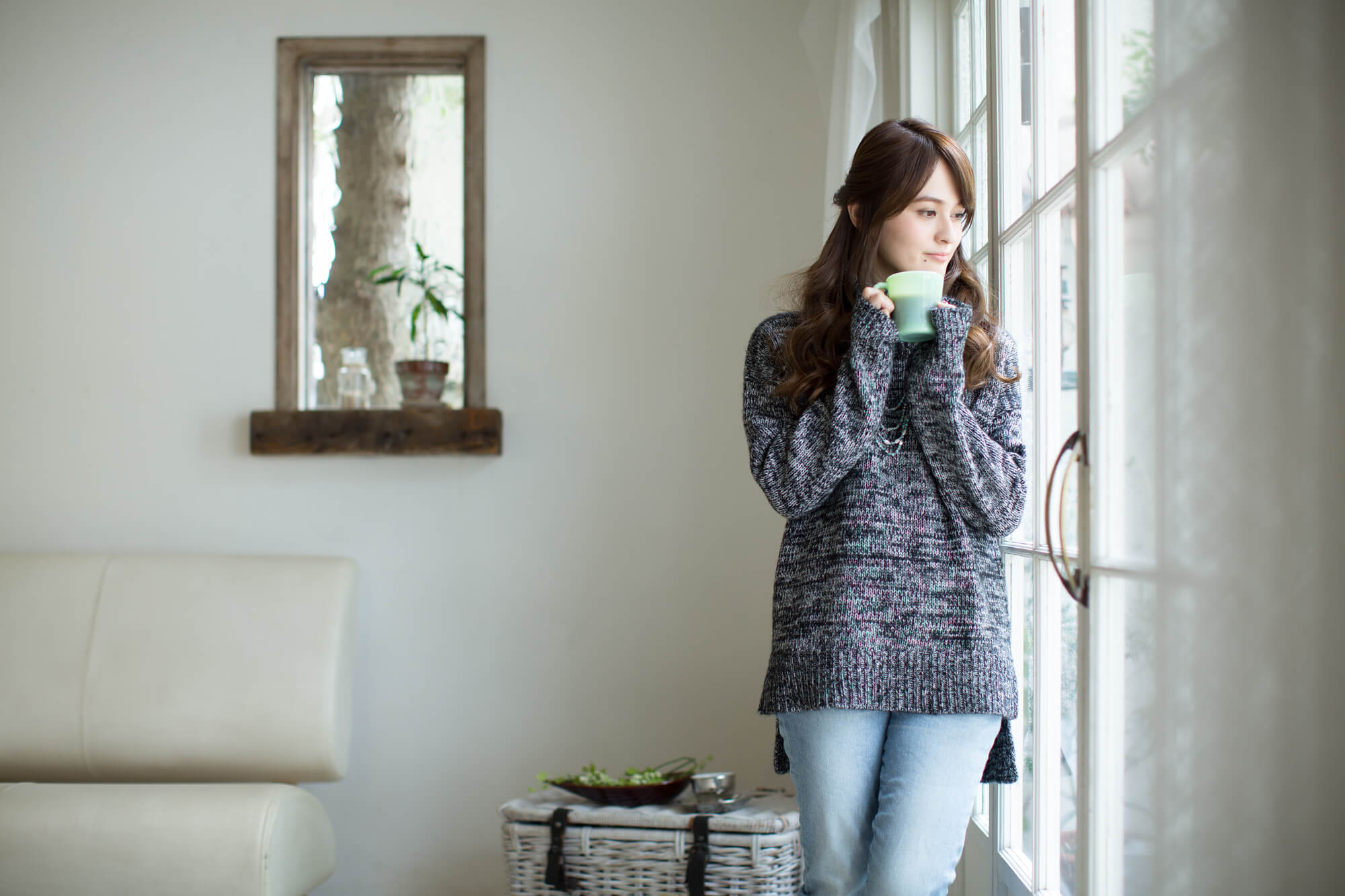 窓辺でホットコーヒーを飲む若い女性
