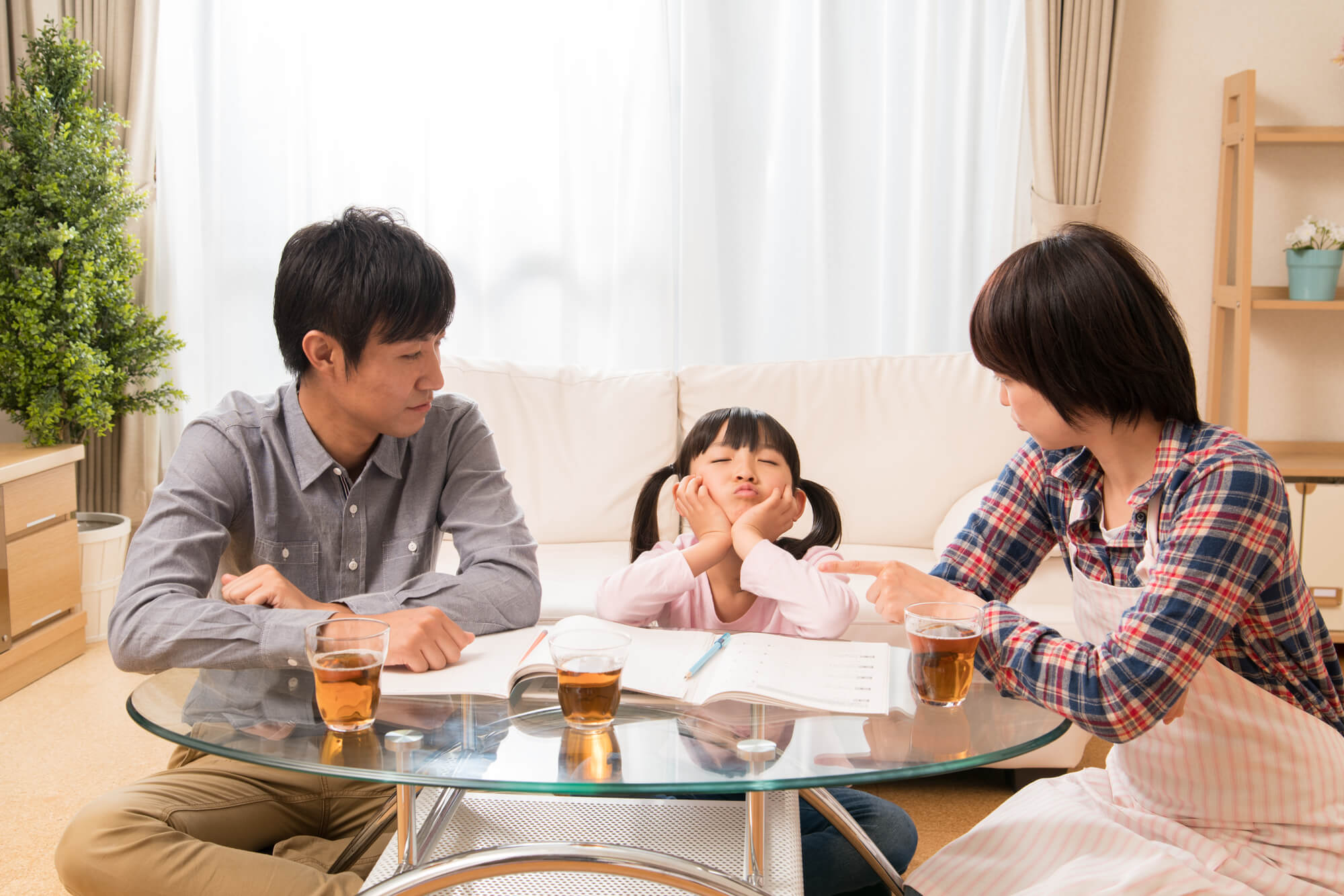 勉強に飽きた子供を見守る夫婦