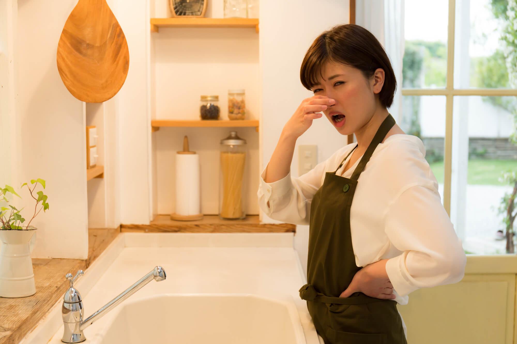 悪臭に耐える女性