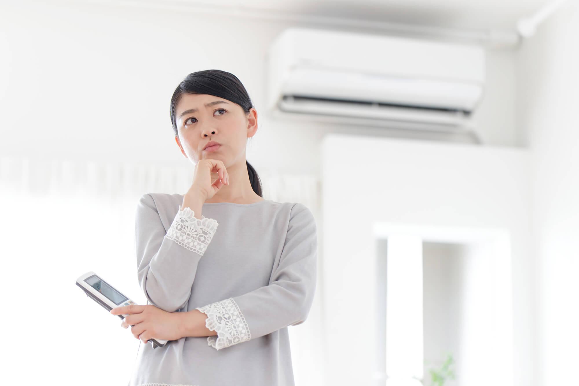 エアコンの使い方に悩む女性