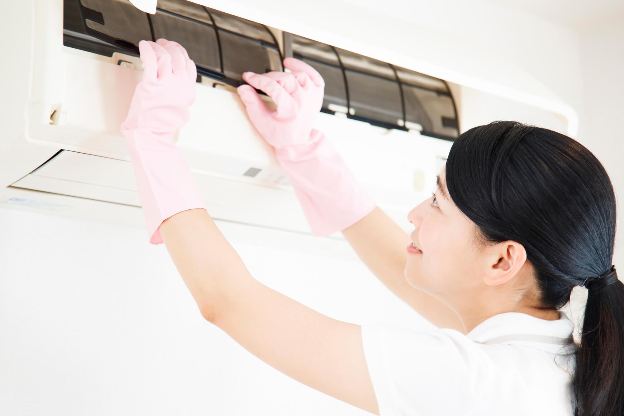 エアコンを掃除中の女性