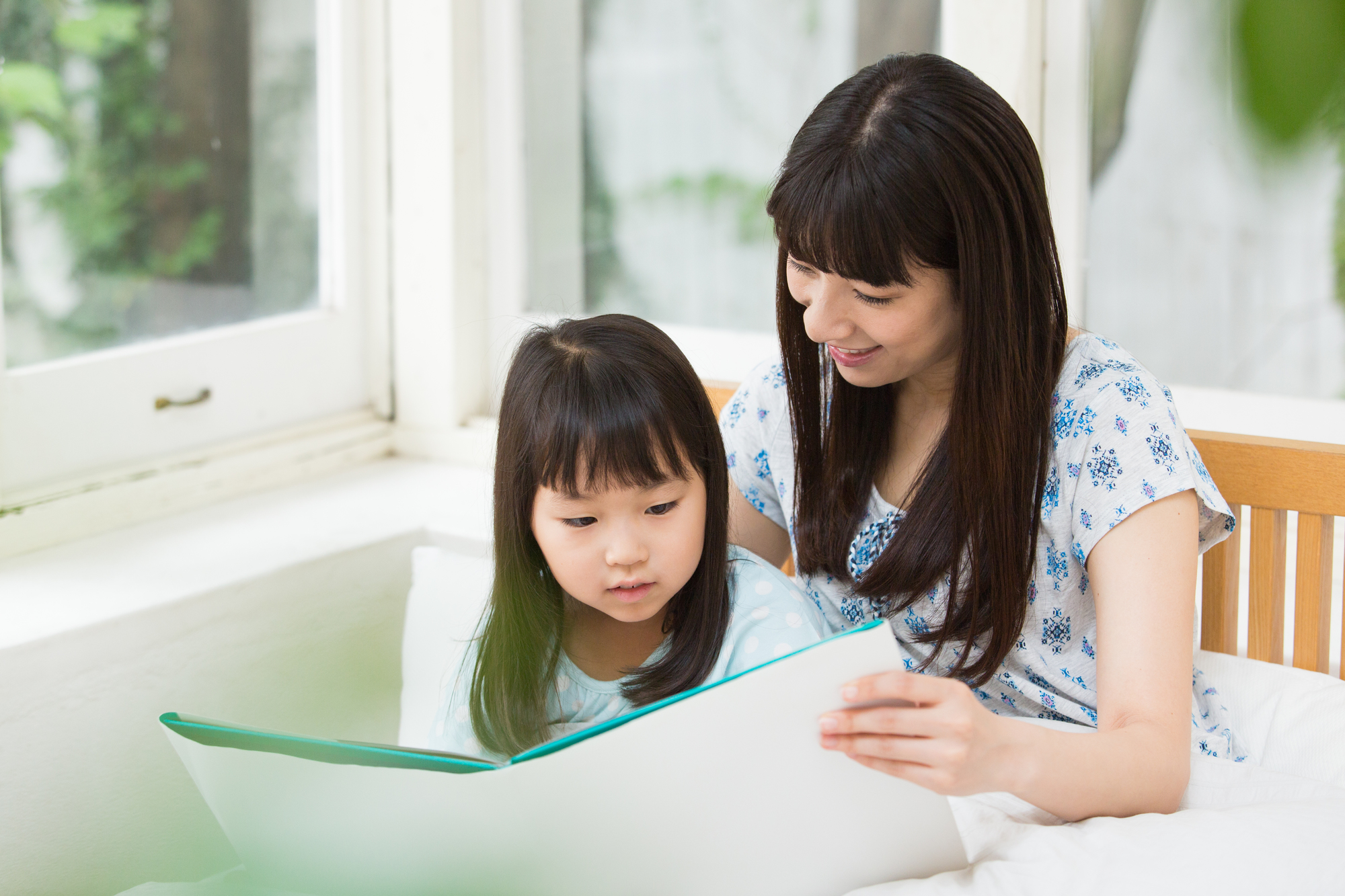 娘に本を読み聞かせる母親