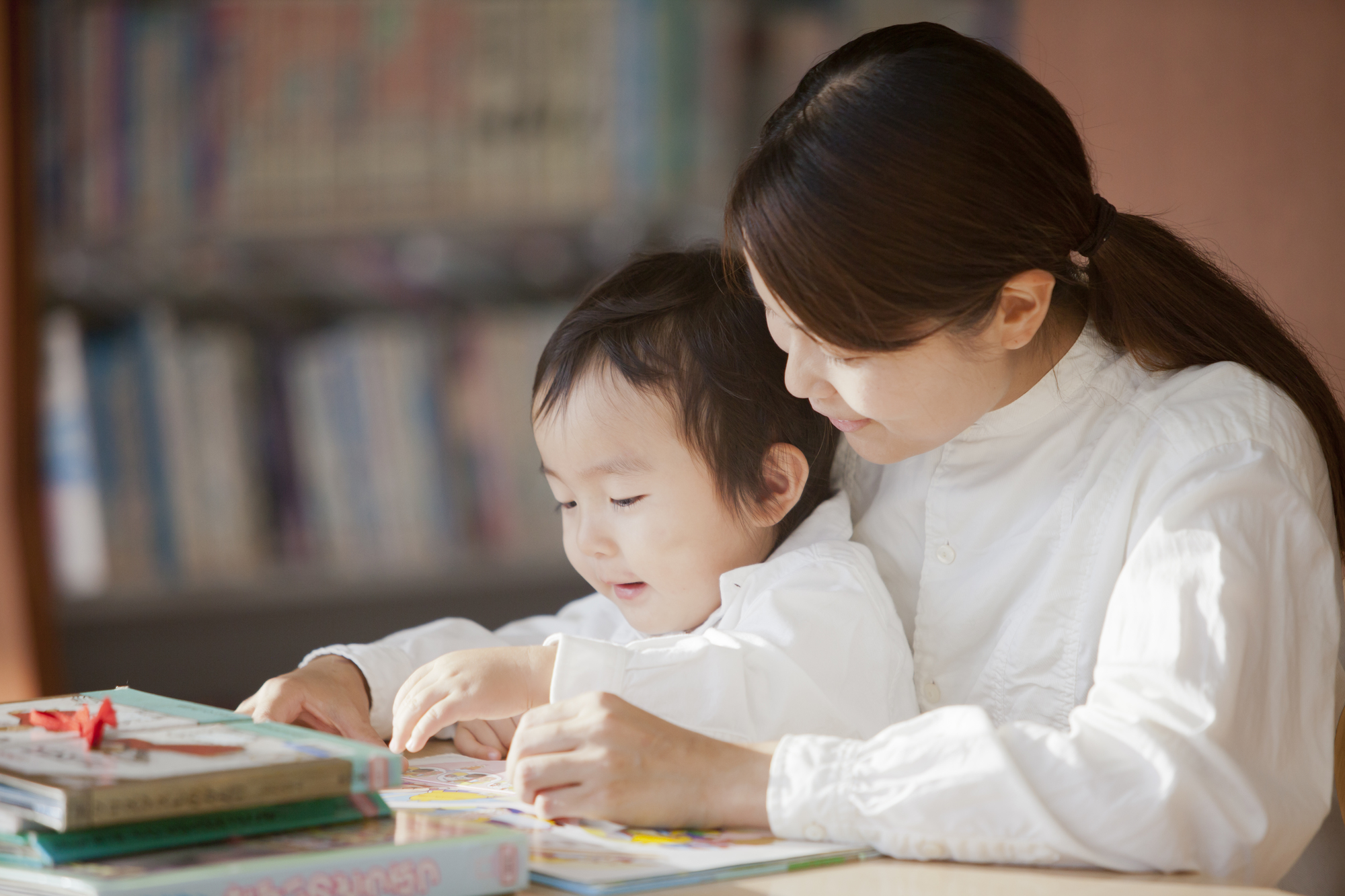 子どもに本を読み聞かせる女性