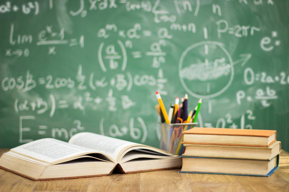 数式の書かれた黒板と辞書